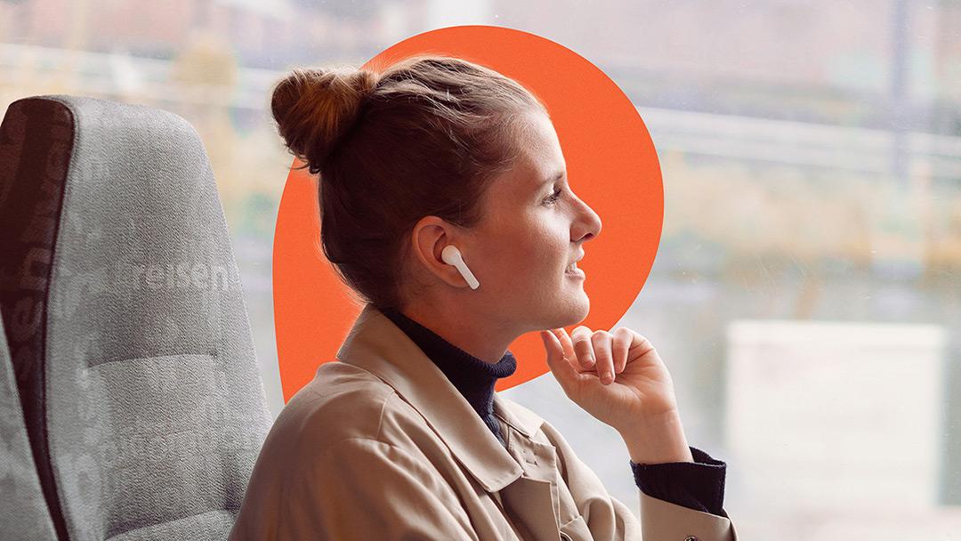 en kvinne hører på lydbøker på toget